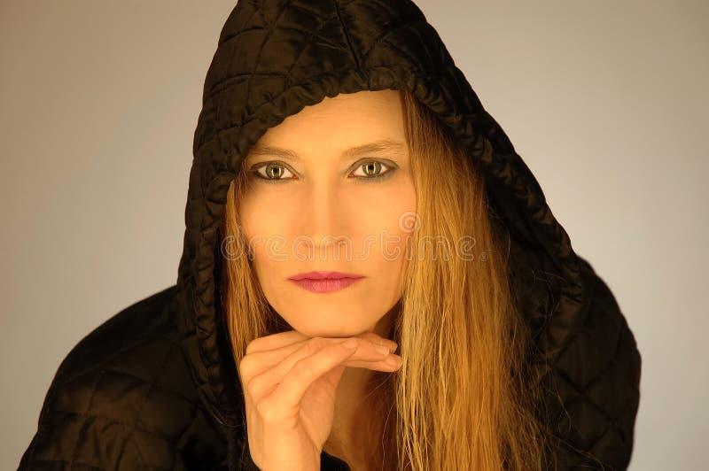 Frau in aufgefülltem Mantel stockbild