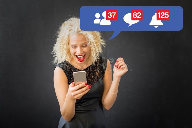 Frau aufgeregt über Tätigkeit auf Social Media lizenzfreies stockbild