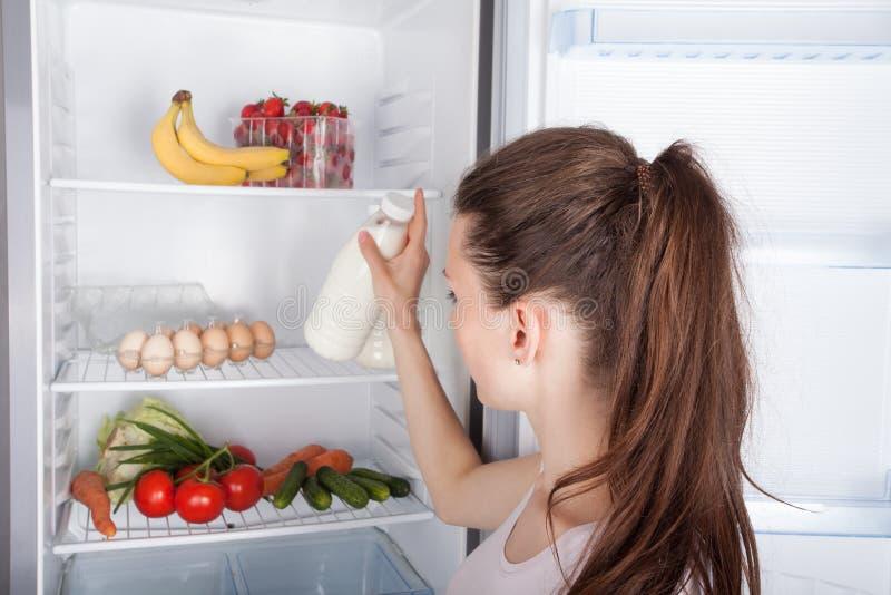 Frau ausgesuchte Milch in geöffnetem Kühlschrank lizenzfreies stockfoto