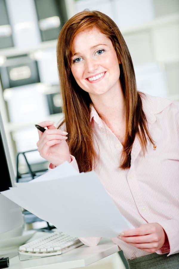 Frau am Büro-Schreibtisch lizenzfreie stockbilder