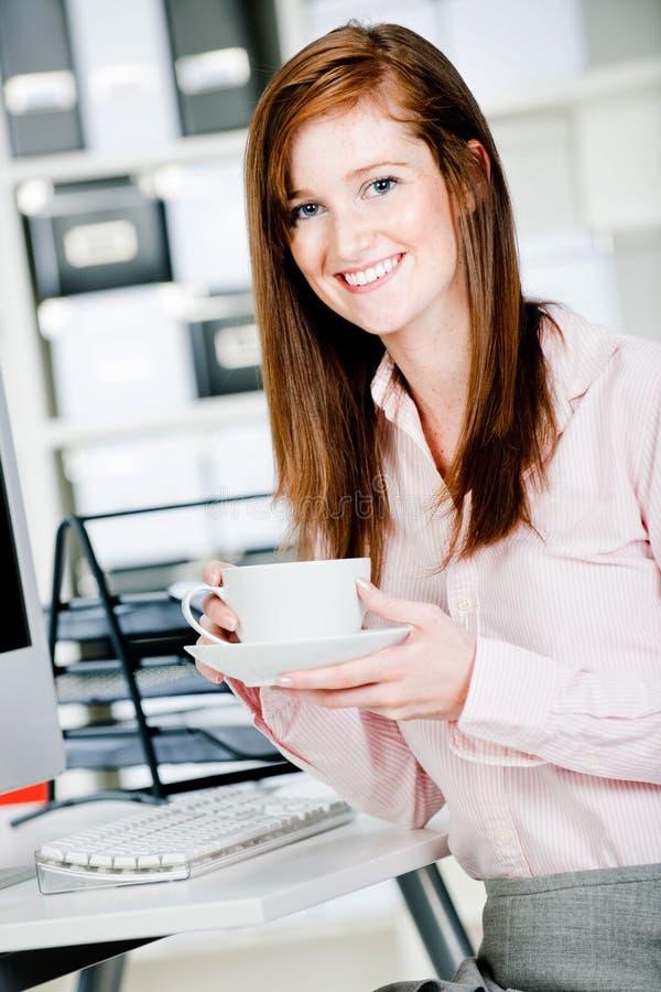 Frau am Büro-Schreibtisch stockfotografie