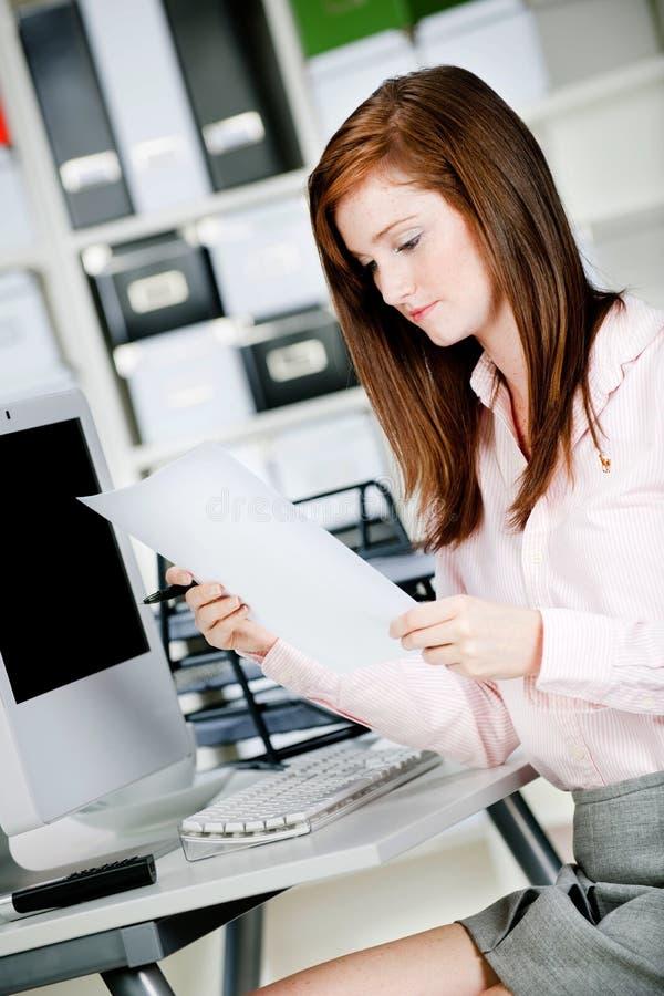Frau am Büro-Schreibtisch lizenzfreie stockfotografie