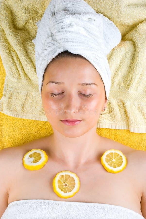 Frau am Badekurort mit Zitrone auf Haut stockbild