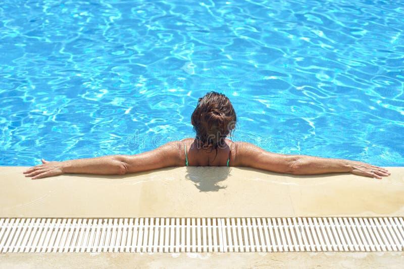 Frau badet im Pool lizenzfreies stockbild