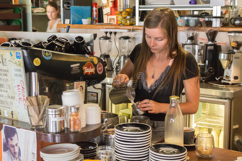 Frau barista, das einen Cappuccino macht lizenzfreies stockbild