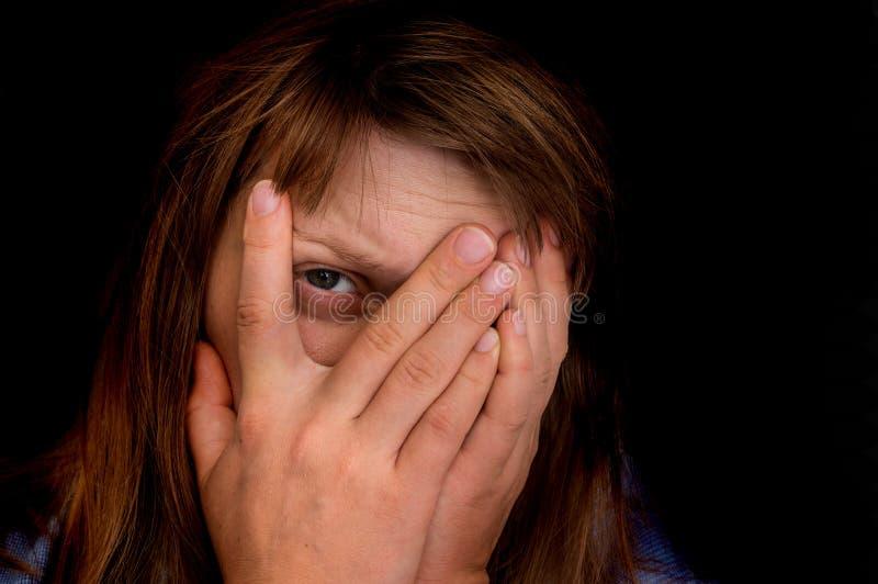 Frau bedeckt ihr Gesicht und betrachtet Kamera mit einem Auge lizenzfreie stockfotografie