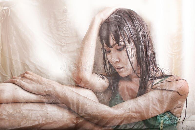 Frau bedeckt mit den Wassertropfen, durchdacht sitzend hinter einem transparenten Vorhang lizenzfreie stockfotografie
