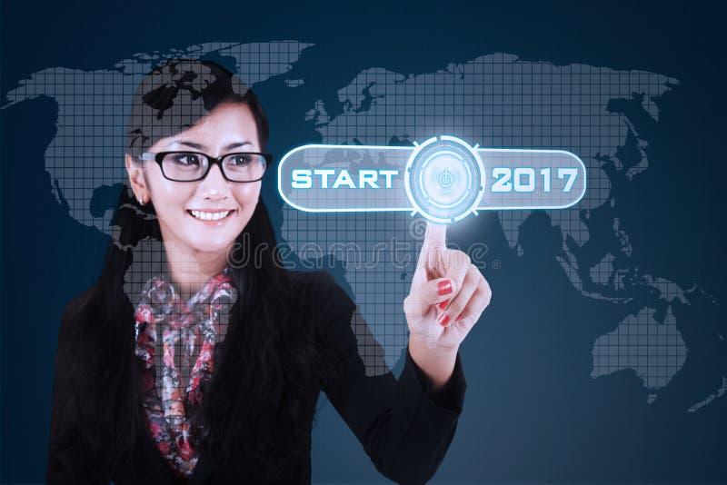 Frau bedrängt Startknopf mit 2017 stockfotos