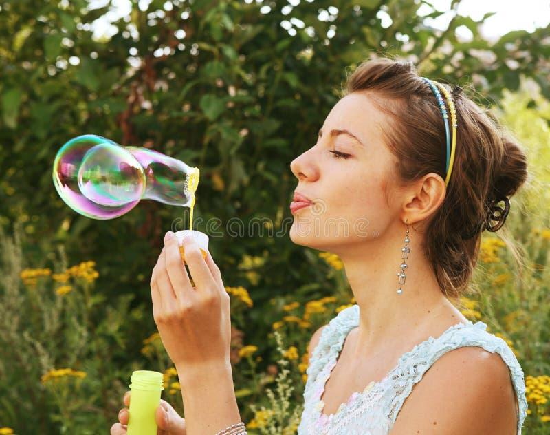 Frau beginnt Seifenluftblasen lizenzfreie stockbilder