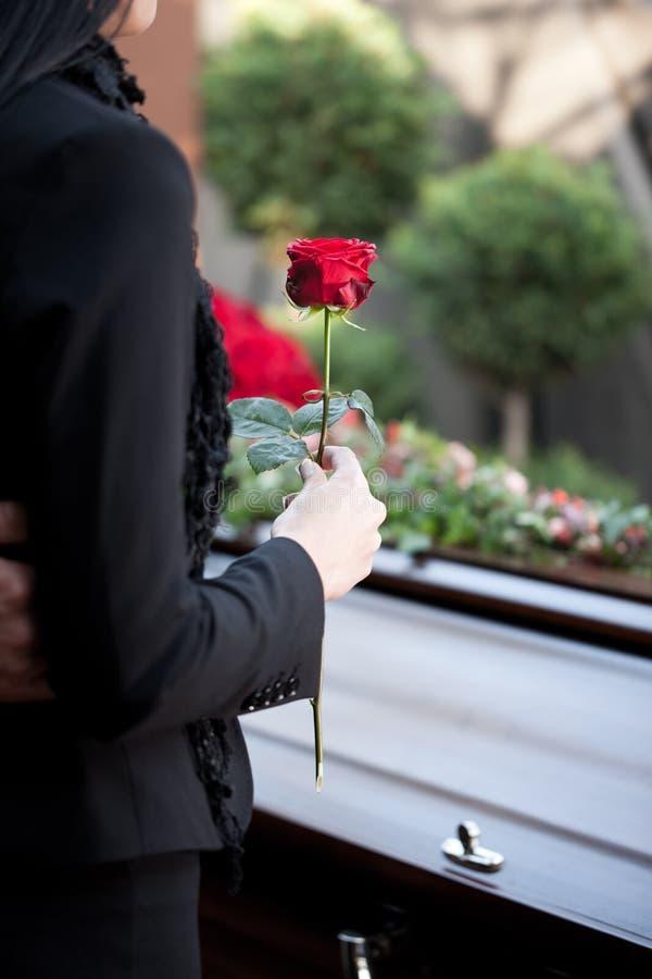 Frau am Begräbnis mit Sarg stockfotografie