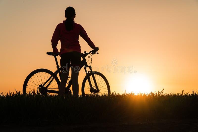 Frau bei Sonnenuntergang vom Sonnenuntergang Fahrradfahrrad übender Sport der Frau stockfoto