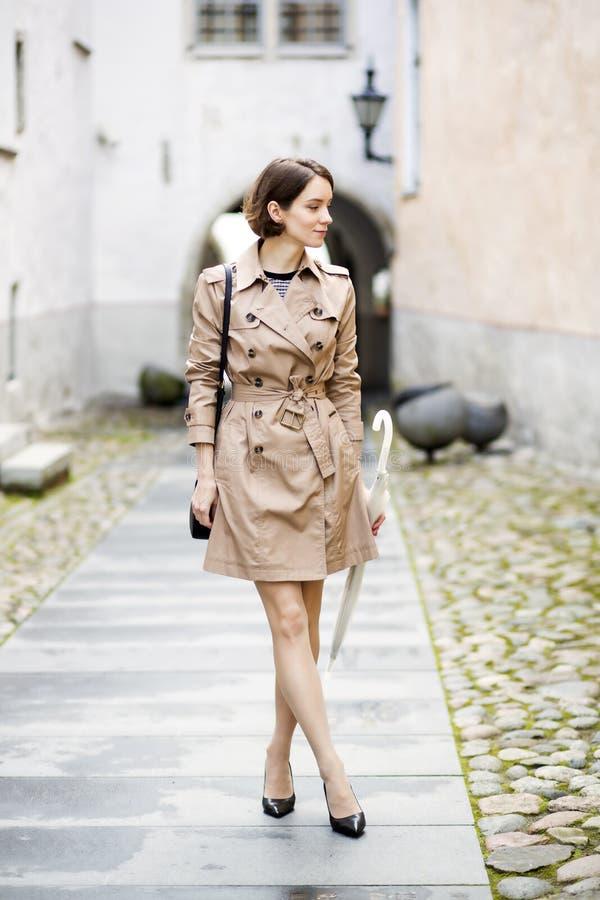 Frau am beige Mantel auf schmalem Straße pasaage stockbilder