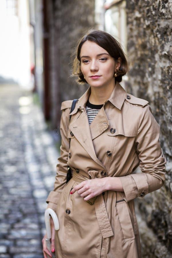 Frau am beige Mantel denkend, wohin man geht lizenzfreies stockbild
