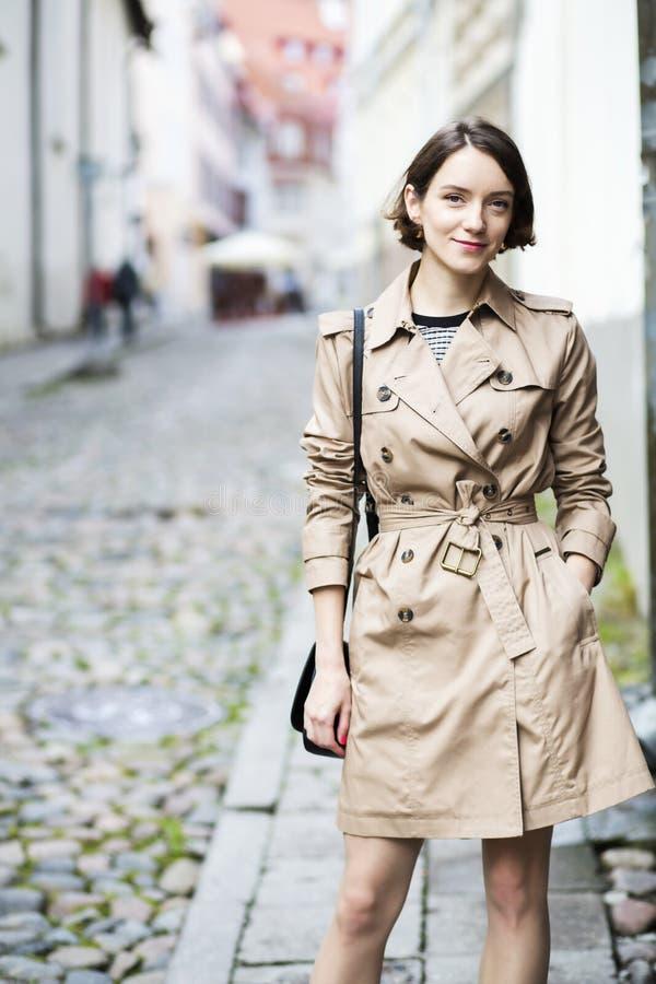 Frau am beige Mantel mit Handtasche lächeln stealthily stockfotografie
