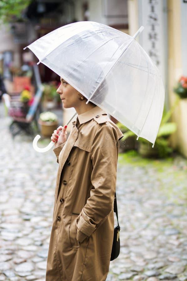 Frau am beige Mantel und an geöffnetem weißem Regenschirm stockfotos