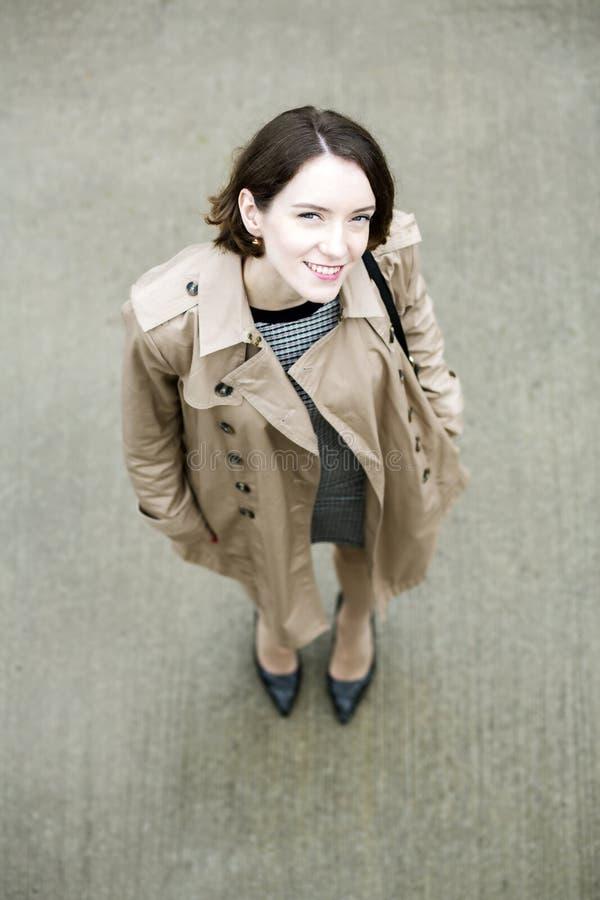 Frau am beige Mantel und am grauen quadratischen Beton stockbild