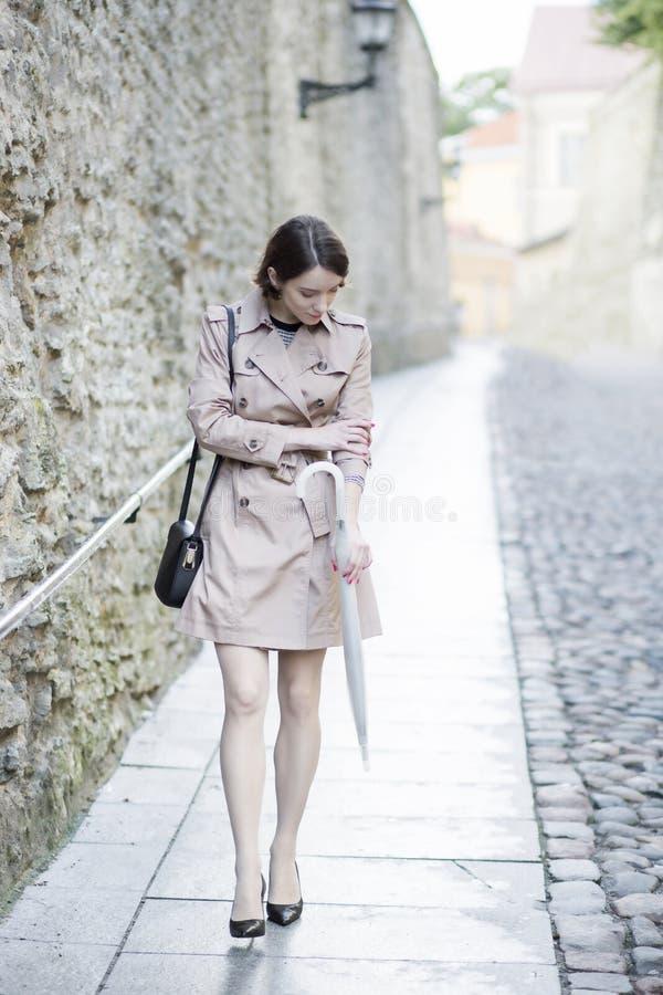 Frau am beige Mantelblick auf blasse Hand stockbilder