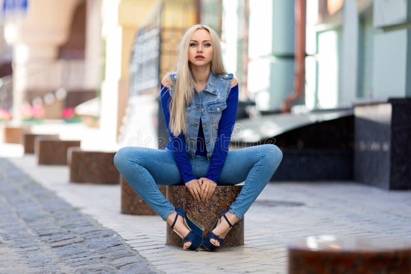 Frau beim Jeanskostümsitzen im Freien lizenzfreie stockfotografie