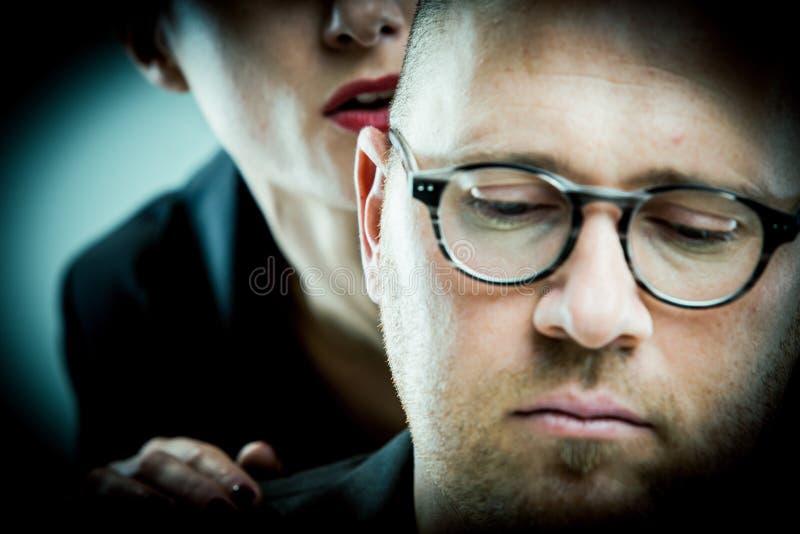 Frau belästigt Mann auf dem Job stockbild