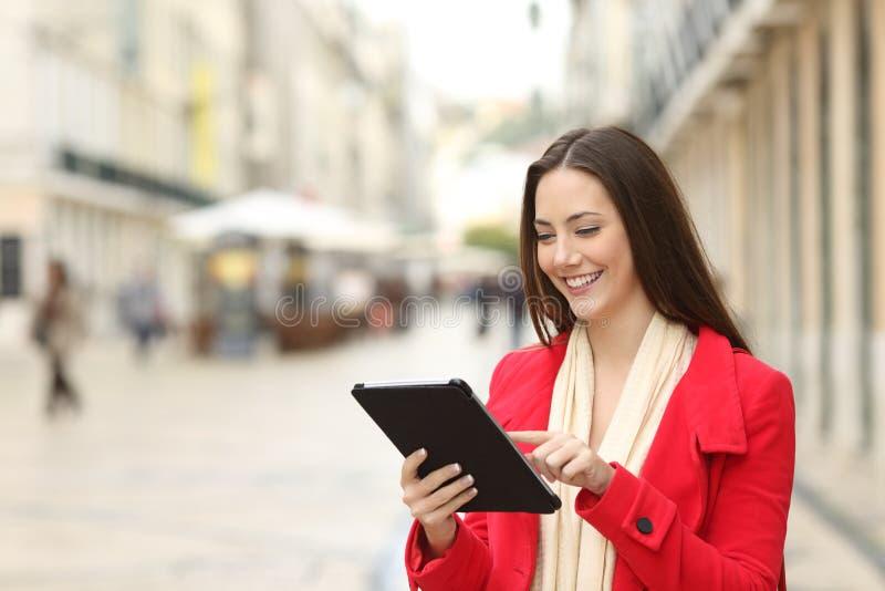Frau benutzt eine Tablette in der Straße im Winter lizenzfreie stockfotografie