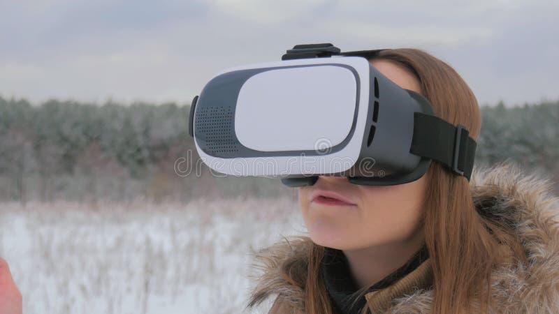 Frau benutzt Gläser einer virtuellen Realität im Winterwald stockfotos