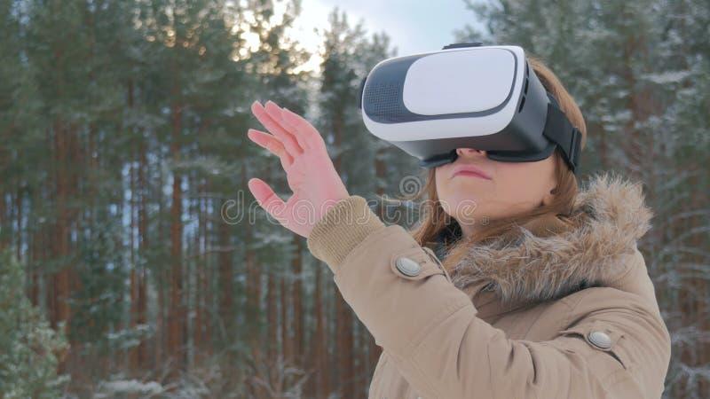 Frau benutzt Gläser einer virtuellen Realität im Winterwald stockfoto