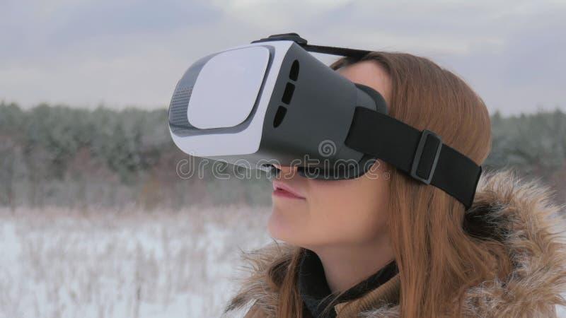 Frau benutzt Gläser einer virtuellen Realität im Winterwald lizenzfreies stockfoto