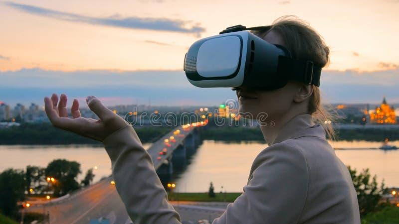 Frau benutzt Gl?ser der virtuellen Realit?t in der Stadt nach Sonnenuntergang stockbild