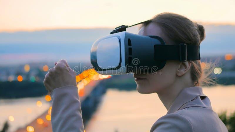 Frau benutzt Gl?ser der virtuellen Realit?t in der Stadt nach Sonnenuntergang stockfotos