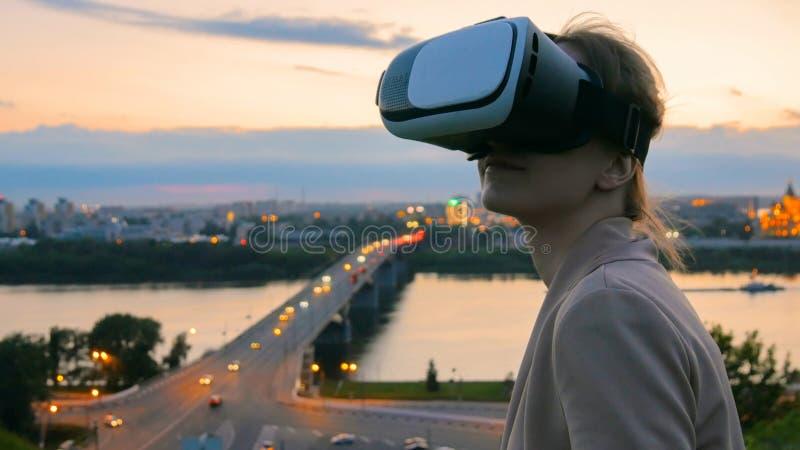 Frau benutzt Gl?ser der virtuellen Realit?t in der Stadt nach Sonnenuntergang lizenzfreies stockbild