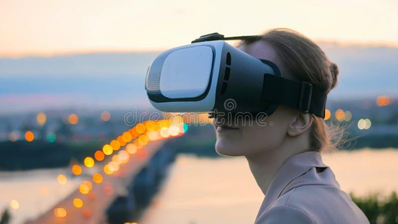 Frau benutzt Gl?ser der virtuellen Realit?t in der Stadt nach Sonnenuntergang lizenzfreie stockfotografie