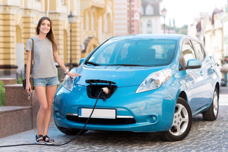 Frau bereit, auf Elektro-Mobil zu gehen stockbild