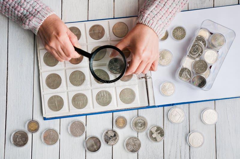 Frau betrachtet die Münzen durch eine Lupe lizenzfreie stockfotografie