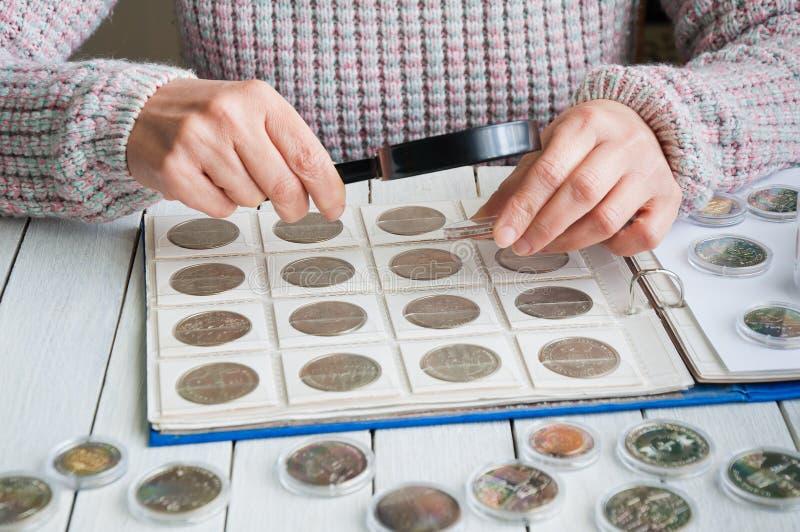 Frau betrachtet die Münzen durch eine Lupe lizenzfreies stockfoto