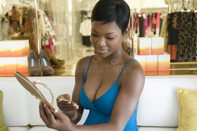 Frau betrachtet Preis auf Jewelled Flip Flops stockbild