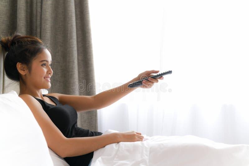 Frau in Bett-aufpassendem Fernsehen und entfernt in halten Fernsehen lizenzfreies stockbild
