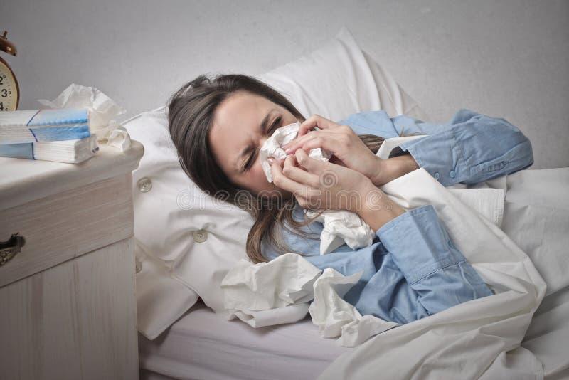 Frau in Bett mit einer Kälte lizenzfreies stockbild