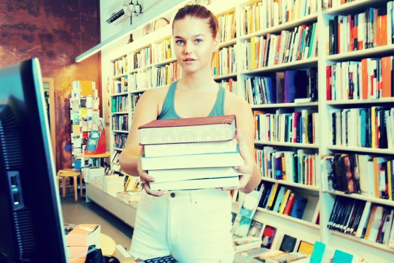 Frau bietet ein Buch in einer Buchhandlung an stockbild