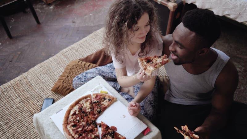 Frau bietet Pizza an, um, aber Scheibe durch zu essen zu bemannen Gemischtrassige Paare, die Spaß während der Mahlzeit mit Schnel lizenzfreie stockfotografie