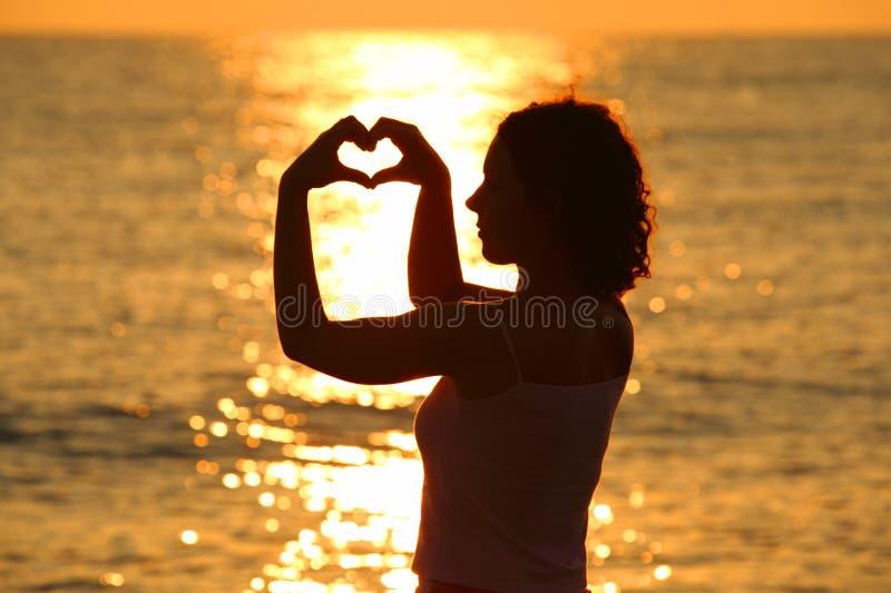 Frau bildet Inneres durch Hände am Sonnenuntergang stockbild
