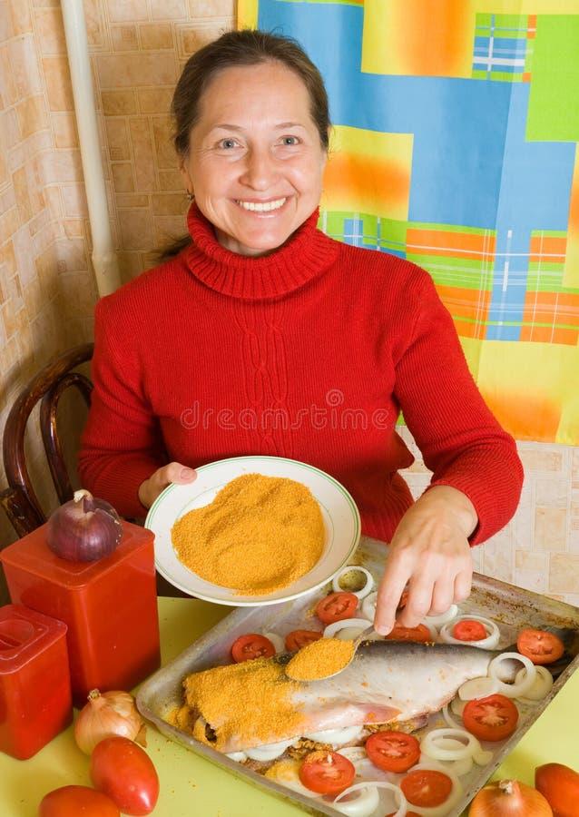 Frau bildet panierte Fische lizenzfreie stockfotografie