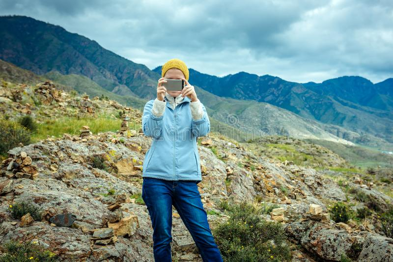 Frau Blogger entfernt Foto und Video durch Smartphone auf dem Hintergrund von Bergen und von bewölktem Himmel Reisender Lebenssti stockfoto