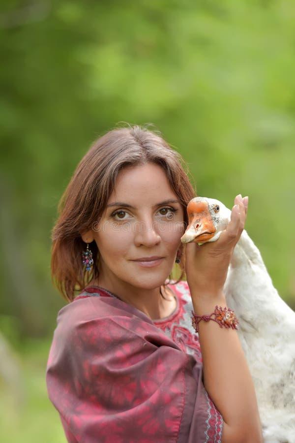 Frau in Burgunder-Kleid auf einem Bauernhof mit einer Gans stockbild