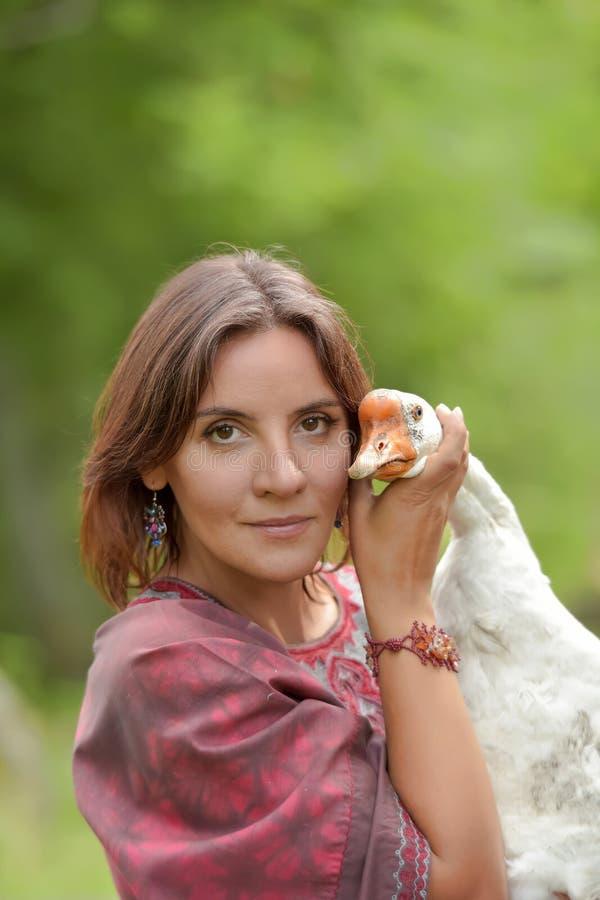Frau in Burgunder-Kleid auf einem Bauernhof mit einer Gans lizenzfreie stockfotografie