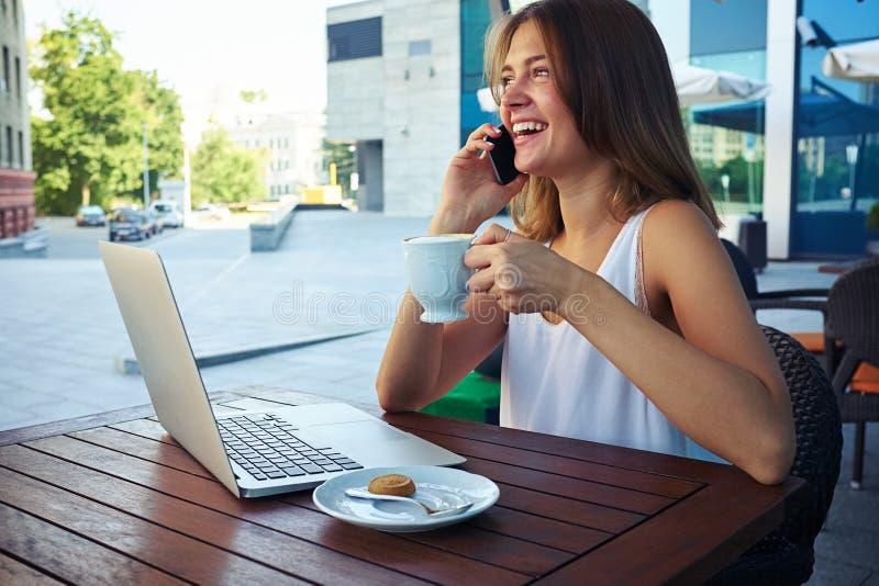 Frau in café im Freien trinkendem Kaffee bei der Unterhaltung auf dem Phon lizenzfreie stockfotos