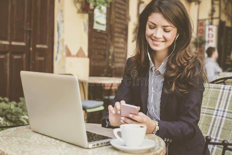Frau am Café, das an Laptop, unter Verwendung des Telefons arbeitet stockfotos