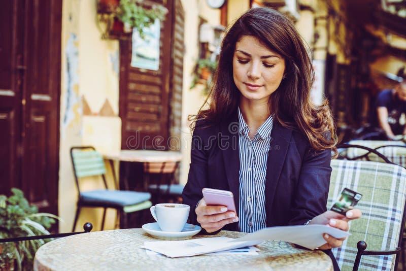 Frau am Café, unter Verwendung des Telefons, zum der Kreditkarte zu überprüfen stockfotografie