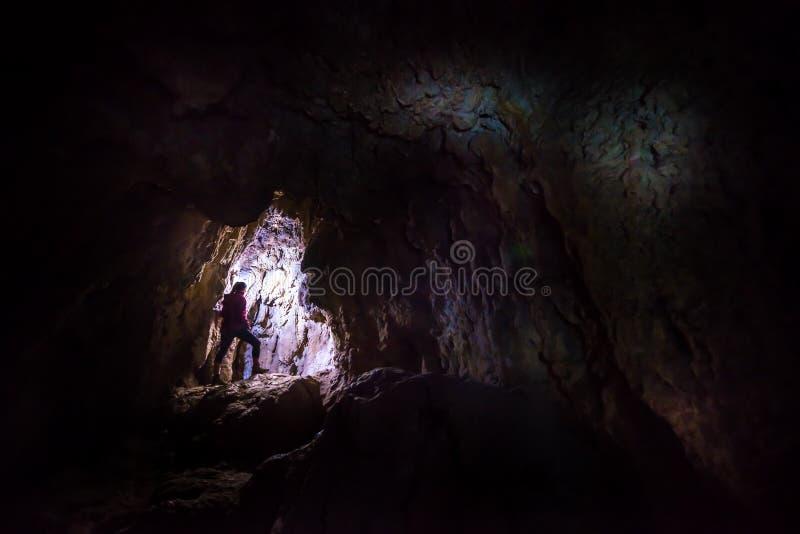 Frau caver Spelunker, der die Höhle erforscht stockfotografie