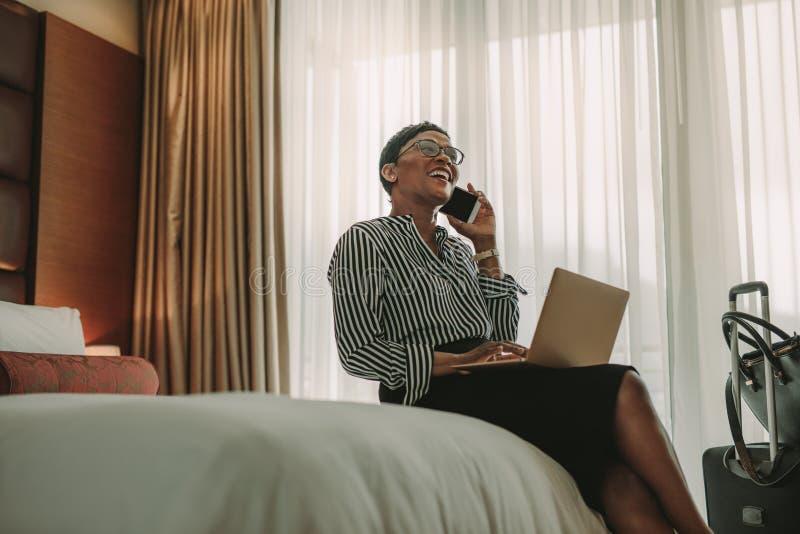 Frau CEO auf der Geschäftsreise, die vom Hotelzimmer arbeitet lizenzfreie stockfotografie