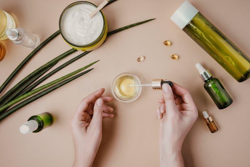 Frau Cosmetologist-Kosmetikprüfung Nat?rliche organische Kosmetik Serumhaarmaske Flacher gelegter Pastell lizenzfreie stockbilder
